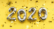canvas print picture - New year 2020 celebration. silver metallic foil balloons numeral 2020 and confetti on yellow background