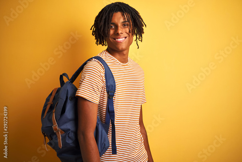 Fotografia  Afro american student man with dreadlocks wearing backpack over isolated yellow