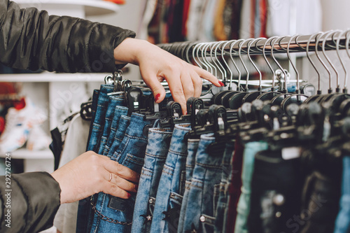 Fototapeta Fast fashion concept. Woman chooses jeans in a store. Lots of clothes in the store. Fast Fashion Destroying Planet. obraz