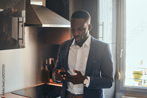 Fotomural  Young african man in white shirt is chatting by mobile phone at the kitchen