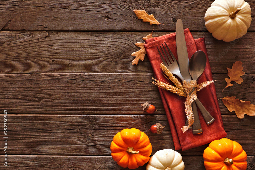 Fototapety, obrazy: Thanksgiving or autumn harvest table setting with silverware, orange napkin, leaves and pumpkin border against a rustic dark wood background