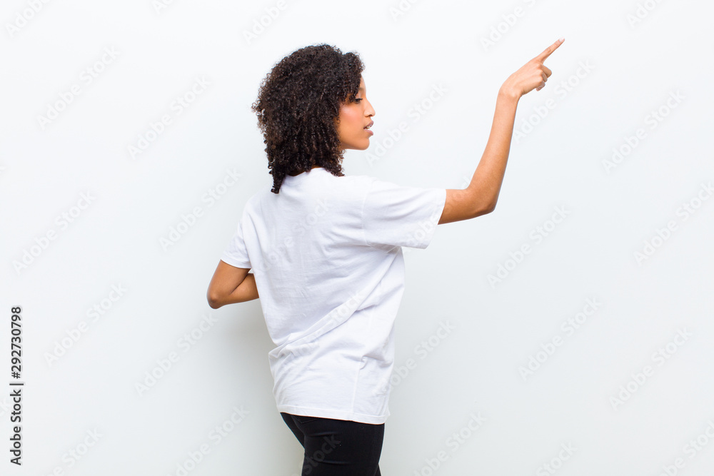 Fototapeta young cool african american woman standing and pointing to object on copy space, rear view
