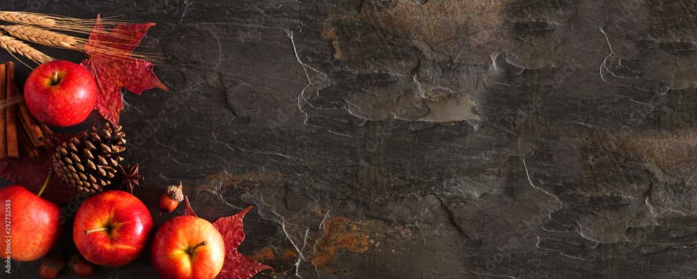 Fototapety, obrazy: Autumn corner border banner of apples, leaves, and fall decor. Top view on a dark stone background with copy space.