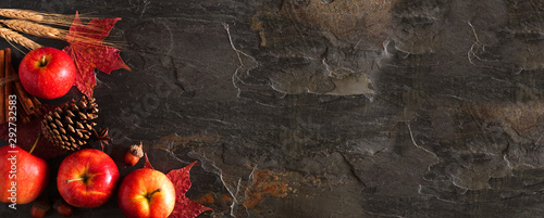 Autumn corner border banner of apples, leaves, and fall decor. Top view on a dark stone background with copy space. - 292732583