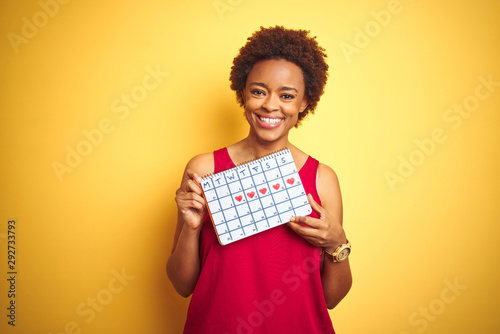 Obraz Young african american woman holding menstruation calendar over isolated yellow background with a happy face standing and smiling with a confident smile showing teeth - fototapety do salonu