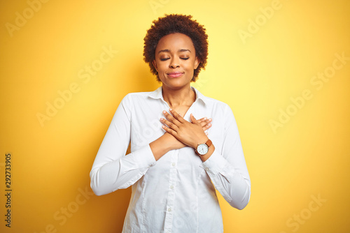 African american business woman over isolated yellow background smiling with hands on chest with closed eyes and grateful gesture on face Tableau sur Toile