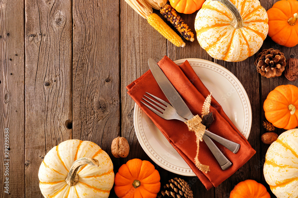 Fototapety, obrazy: Autumn harvest or thanksgiving table setting with silverware, orange napkin, pumpkins and decor. Top view, corner border against a rustic wood background.