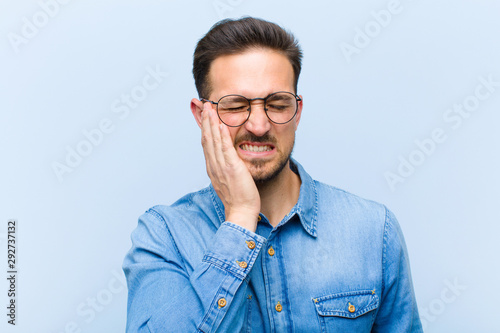 Fotografía young handsome man holding cheek and suffering painful toothache, feeling ill, m