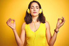 Young Beautiful Woman Listening To Music Using Headphones Over Yellow Isolated Background Relax And Smiling With Eyes Closed Doing Meditation Gesture With Fingers. Yoga Concept.