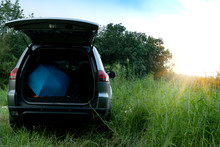 The Back Of The Family Car With The Tailgate Open And Have Umbrellas And Various Equipment. With Nature Green Fields And Sun Shining.
