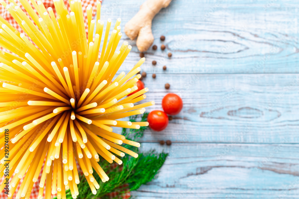 Fototapety, obrazy: Long pasta in the shape of a bouquet, red cherry tomatoes, ginger root and peas of black pepper with dill greens on a napkin on a light blue wooden table. Ingredients for healthy food. Copy space.
