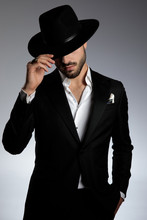 Mysterious Young Man Pulling Hat Down And Saluting