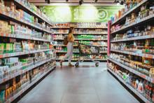 Woman With Shopping Between Store Shelf