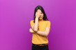 Leinwanddruck Bild - young pretty latin woman looking stressed, ashamed or upset, with a headache, covering face with hand against purple wall