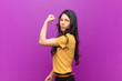 canvas print picture - young pretty latin woman feeling happy, satisfied and powerful, flexing fit and muscular biceps, looking strong after the gym against purple wall