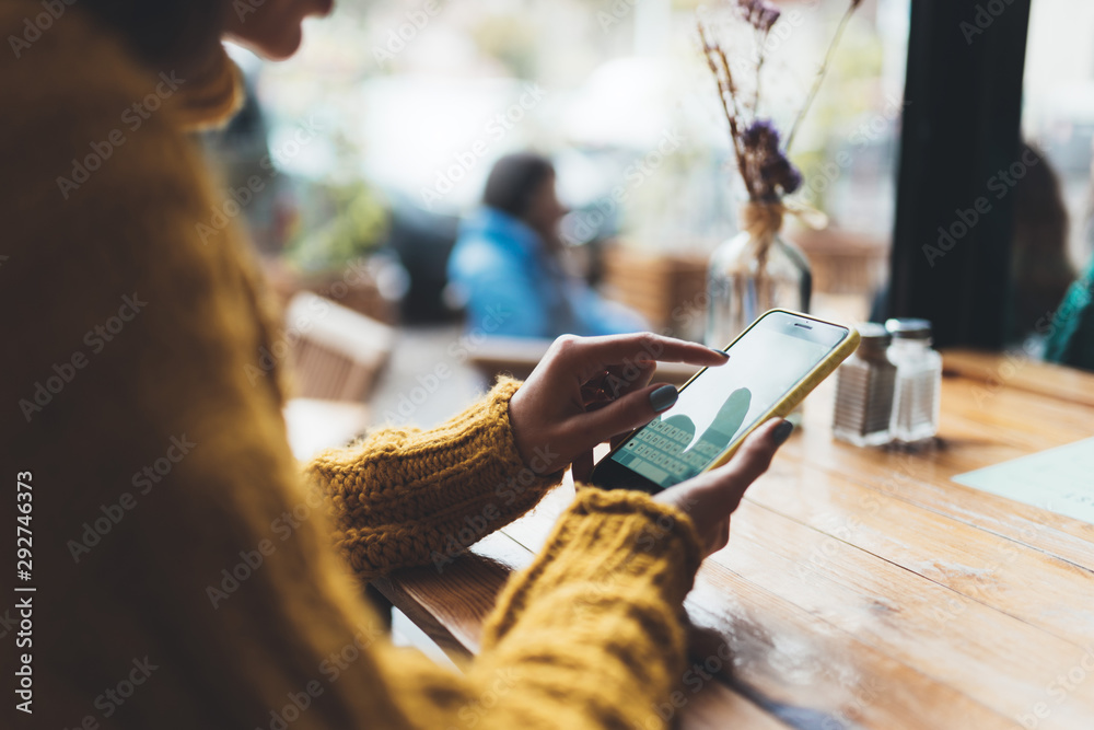Fototapeta girl hold in hands mobile phone empty screen, person type message on smartphone cafe, tourist travels planning trip, hipster enjoy journey in cityscape, lifestyle holiday concept, internet online