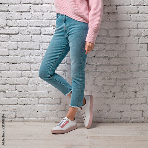 Female legs in turquoise jeans, pink sweater and sneakers leaning to white brick Obraz na płótnie