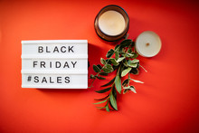 Black Fiday Light Box With Leaves And Candles On Red Background