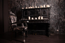Old Black Vintage Piano With White Candles And Retro Chair. Nobody