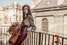 Outdoor Fashion Portrait Of Young Elegant, Luxury Brunette Woman Wearing Dark Red Faux Leather Beret, Skirt, Snakeskin Print Blouse, Beige Sunglasses, Holding Brown Handbag. Copy, Empty Space For Text