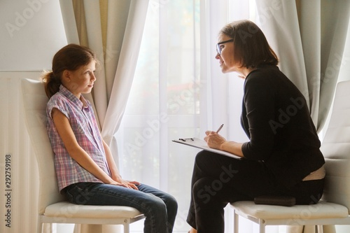Obraz Teacher teaching and talking to a girl child, private individual lesson - fototapety do salonu