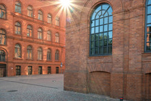 Allyeway With Red Brick Industrial Buildings With Sun Flare Background