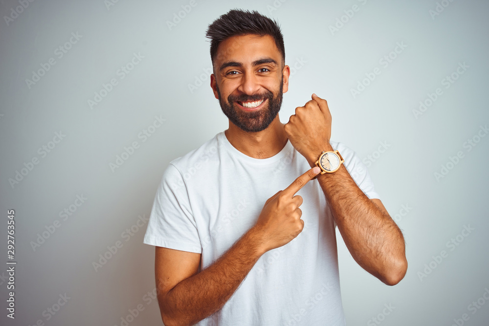 Fototapeta Young indian man wearing t-shirt standing over isolated white background In hurry pointing to watch time, impatience, looking at the camera with relaxed expression