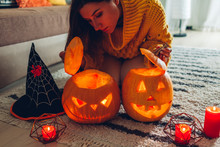 Halloween Jack-o-lantern Pumpkins. Woman Opens Pumpkins And Looks Inside At Home. Mysterious Holiday