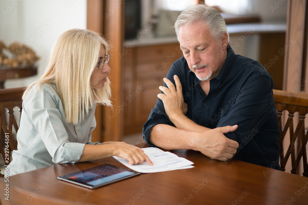 Fototapety, obrazy: Senior couple calculating their living expenses together