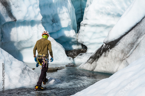 Ice climber walking through a river toward a large ice cave on the Matanuska Glacier in Alaska.