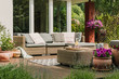 Leinwanddruck Bild - Classy furniture on wooden terrace in green beautiful garden
