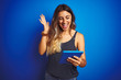 canvas print picture - Young beautiful woman using touchpad tablet over blue isolated background very happy and excited, winner expression celebrating victory screaming with big smile and raised hands