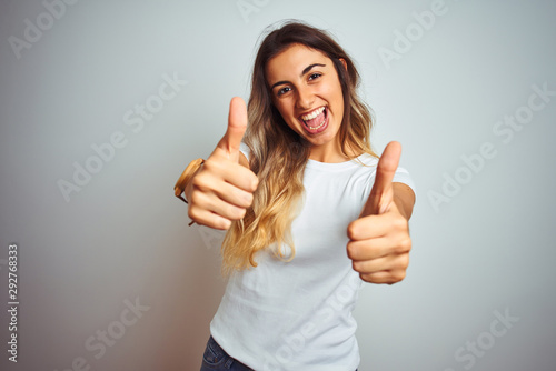 Obraz Young beautiful woman wearing casual white t-shirt over isolated background approving doing positive gesture with hand, thumbs up smiling and happy for success. Winner gesture. - fototapety do salonu