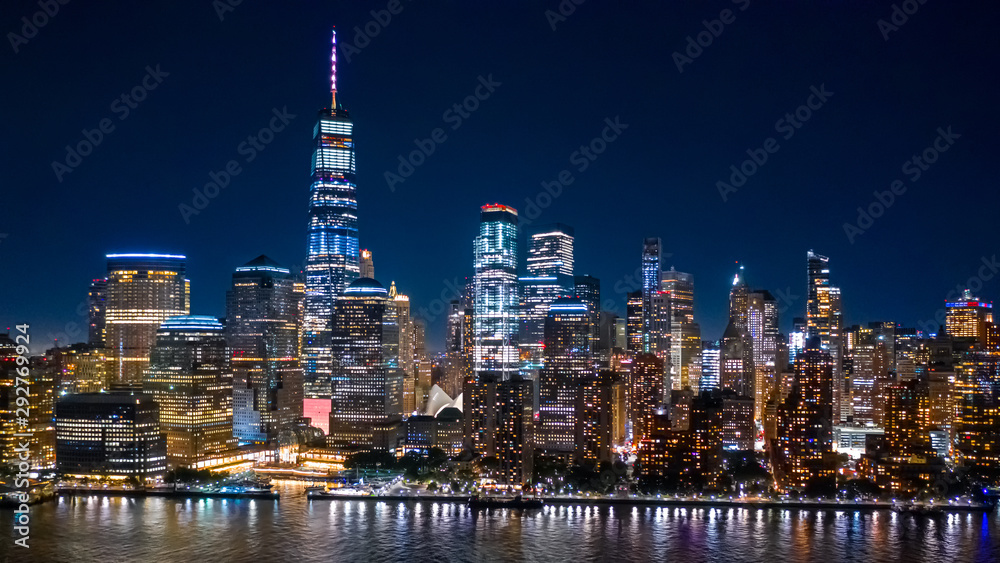Fototapeta Aerial view of Lower Manhattan skyline by in night in New York City