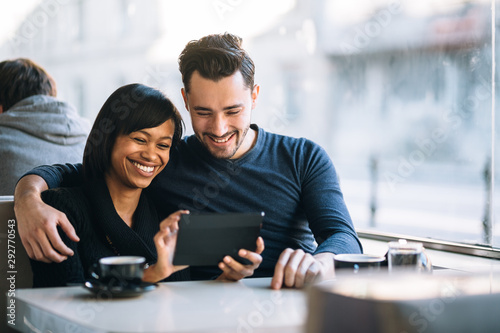 Fotografie, Obraz  Interracial couple using tablet computer in coffee shop