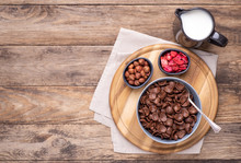 Chocolate Breakfast Cereal In A Bowl On Rustic Wooden Table, Top View With Copy Space