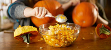 Family Fun Activity For Halloween- Two Sisters Removing Insides Of Pumpkin And Placing It Inside Bowl With Focus On Spoon