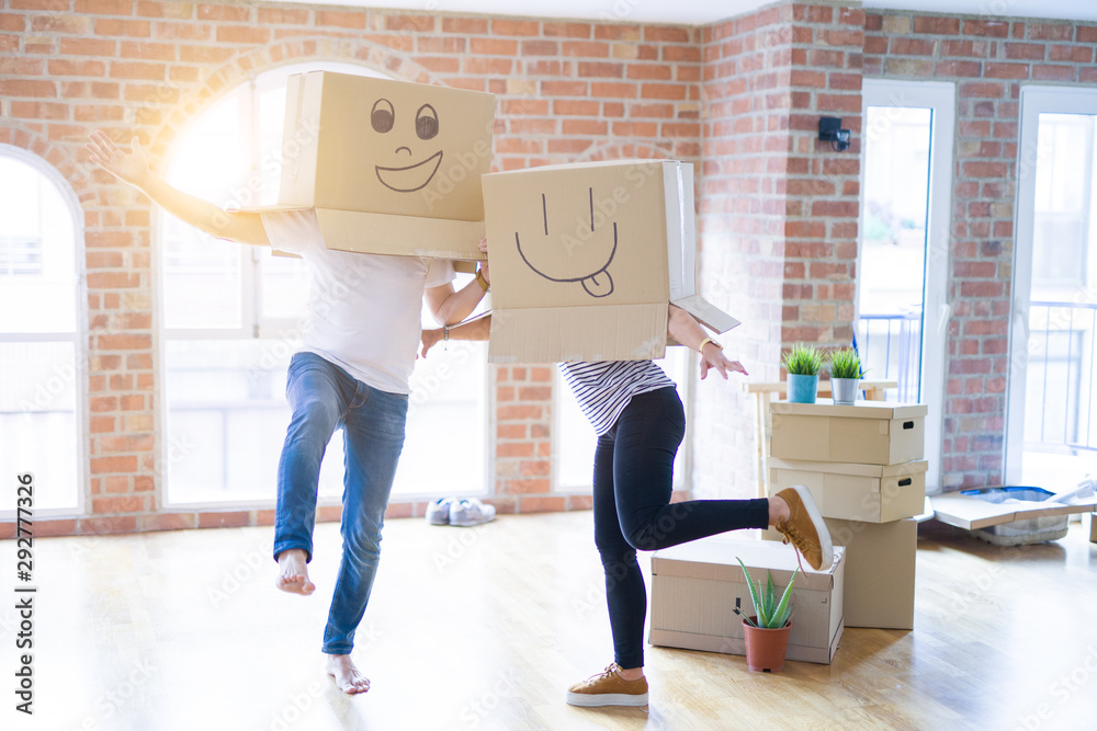 Fototapeta Couple wearing funny cardboard boxes with happy faces, moving to a new house, crazy and creative concept