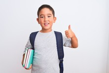Beautiful Student Kid Boy Wearing Backpack Holding Books Over Isolated White Background Happy With Big Smile Doing Ok Sign, Thumb Up With Fingers, Excellent Sign