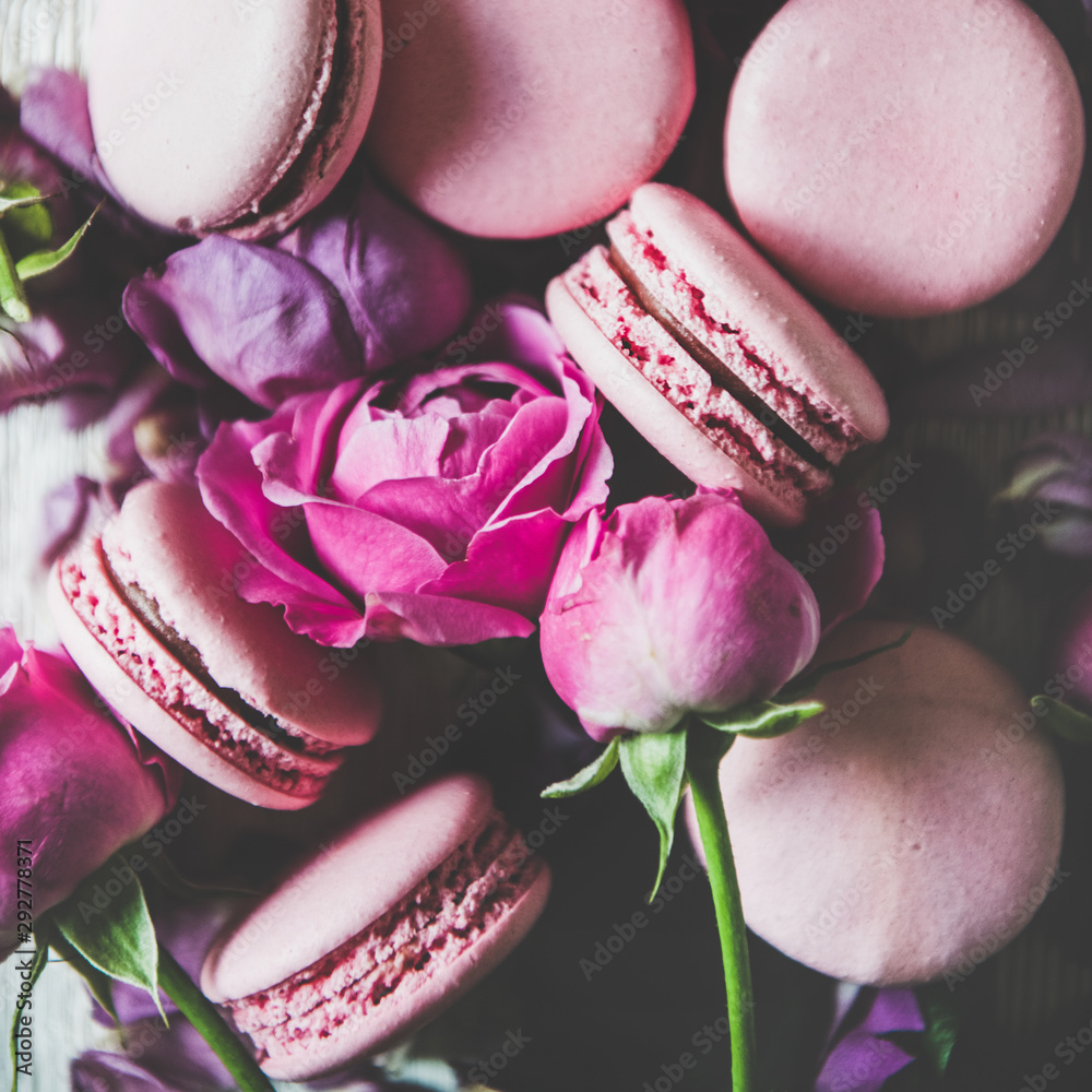 Fototapety, obrazy: Sweet pink macaron cookies and spring rose flowers, buds and petals over wooden background, top view, selective focus, close-up, square crop. Food texture, background and wallpaper