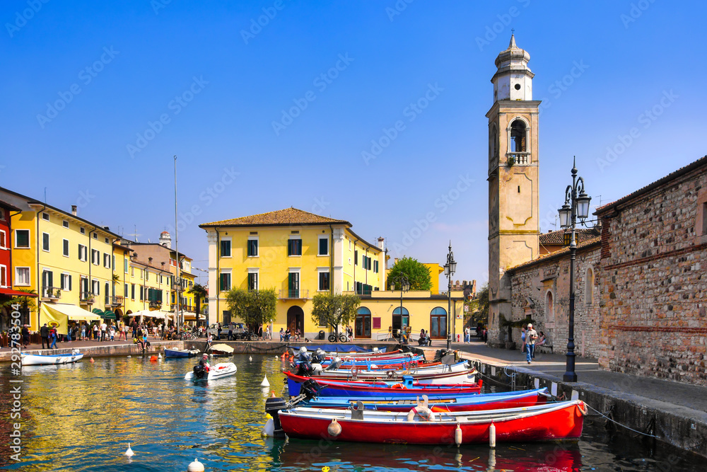 Fototapety, obrazy: Boats in old town port of Lazise and tourists walking in the morning. The town is a popular holiday destination in Garda Lake district.
