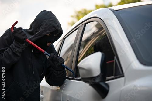 Fotografía  Auto thief in black balaclava trying to break into car