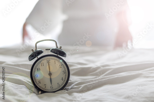 Obraz Woman on bed wake up stretching in bedroom with alarm clock at 6.00 a.m. morning. Biological Clock healthcare lifestyle concept - fototapety do salonu