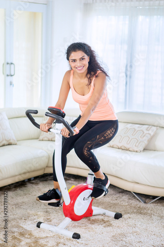 Fotografia, Obraz Happy woman doing a workout with exercise bike