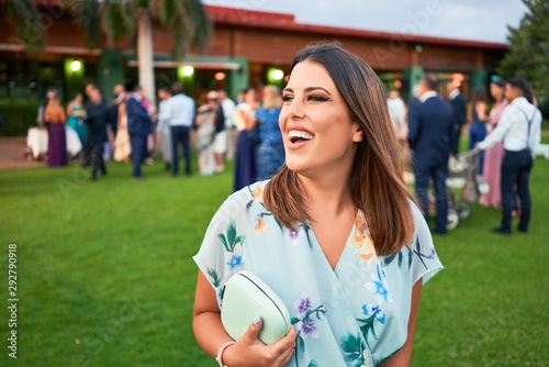 Young beautiful and elegant woman with wedding guest dress smiling happy and che Fototapet