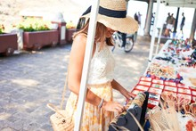 Young Beautiful Woman At Traditional Handmade Market Shopping At Souvenir Kiosk