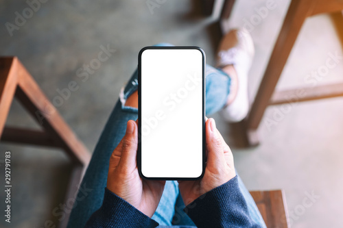 Obraz Top view mockup image of a woman holding black mobile phone with blank white screen while sitting in cafe - fototapety do salonu