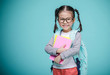 Leinwandbild Motiv Beautiful smiling Asian little girl with glasses and hold a books with school bag is back to school, empty space in studio shot isolated on colorful blue background, Educational concept for school