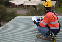 Rope Access Inspector Technician Holding Looking At The Paper Work While Inspecting Fall Arrest, Fall Restraint Roof Anchor Point Horizontal Safety Line Sydney, CBD, Australia