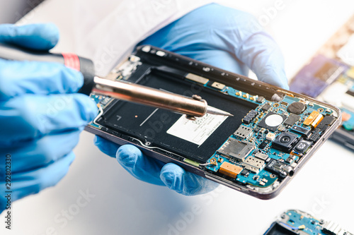 Fotografía  The technician repairing the smartphone's motherboard in the lab by soldering method